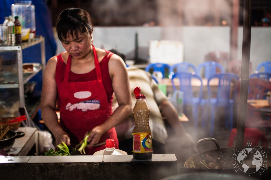 Kobieta przygotowująca posiłki w małej restauracji na lokalnym targu, Wietnam